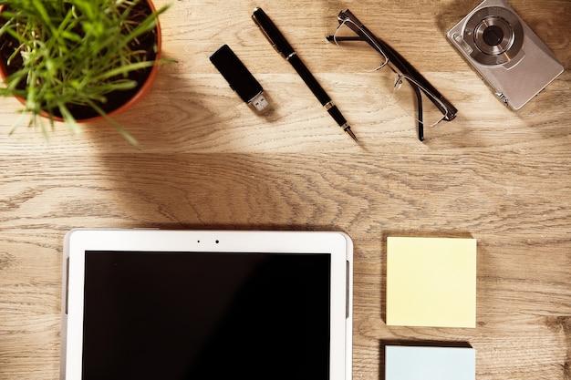 Business still - digitales tablet und notizpapier auf holz