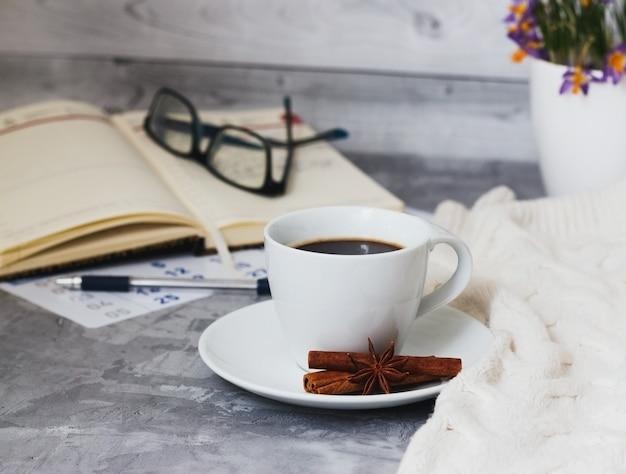 Business-stillleben mit tasse schwarzem kaffee, notizbuch, stift, brille auf grauem betontisch