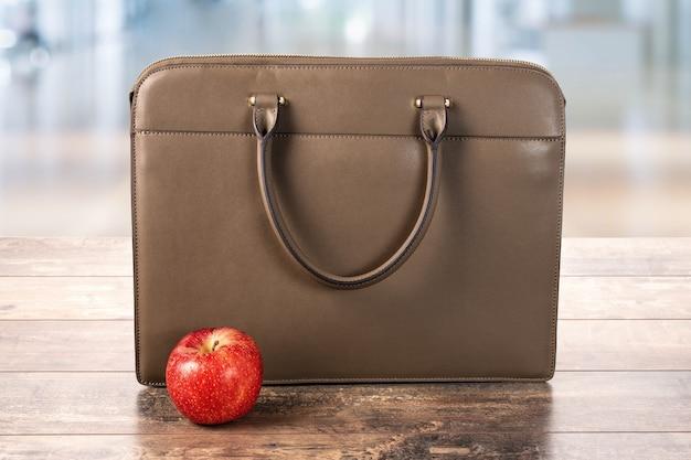 Business-tasche, aktentasche und roter apfel auf einem holztisch