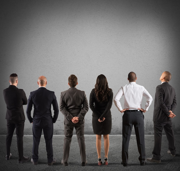 Business-team blick auf die graue leere wand