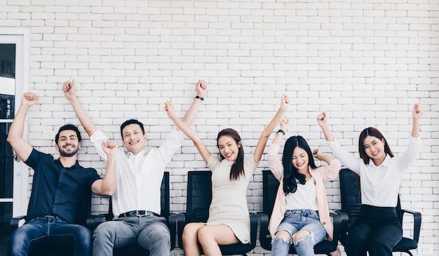 Business-team feiert einen triumph mit erhobenen armen, gruppe glücklicher geschäftsleute in smart casual