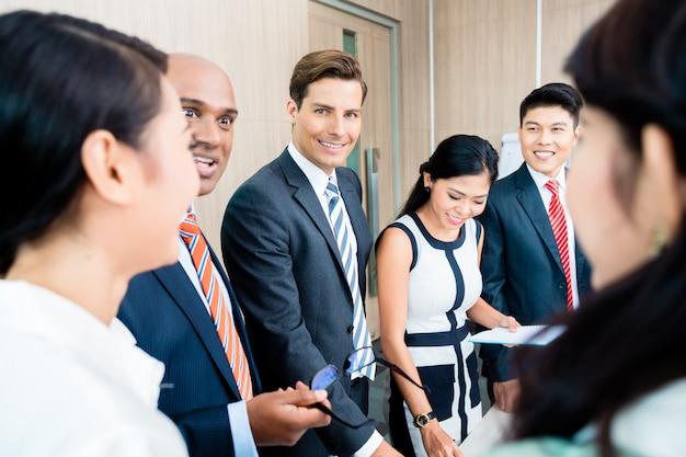 Business-team-meeting von asiatischen und kaukasischen führungskräften