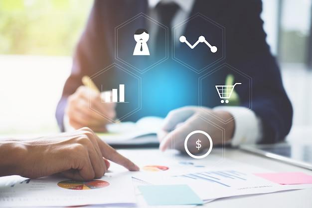 Business team support und meeting-konzept. investor zwei, der an der schreibarbeit finanzaufgabe mit finanzikone arbeitet.