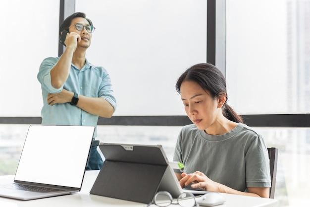 Business-teamwork, das am laptop im bürogebäude arbeitet Premium Fotos