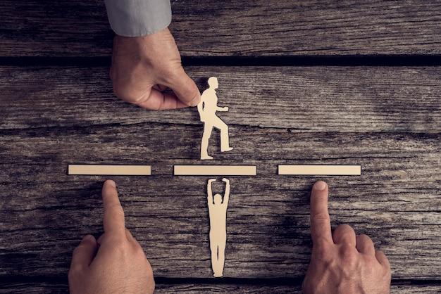 Business-teamwork-konzept mit den händen von drei geschäftsleuten, die papierausschnitte von zwei männern über rustikalem holz mit kopierraum unterstützen oder unterstützen.