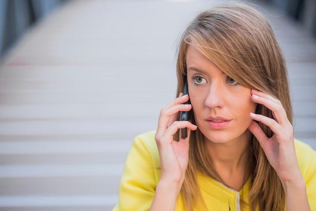 Business, technologie und menschen konzept - ernst geschäftsfrau mit smartphone sprechen über bürogebäude