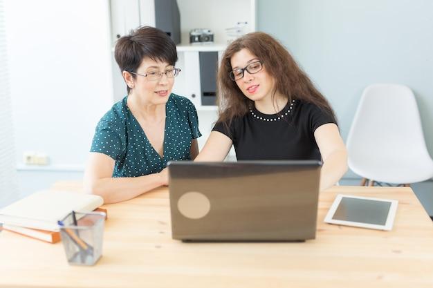 Business-, technologie- und people-konzept - zwei frauen diskutieren über ein projekt, das sie sich auf einem laptop ansehen