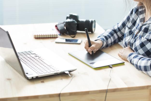 Business-, technologie- und personenkonzept - frau verwendet designer-tablet bei der arbeit am laptop