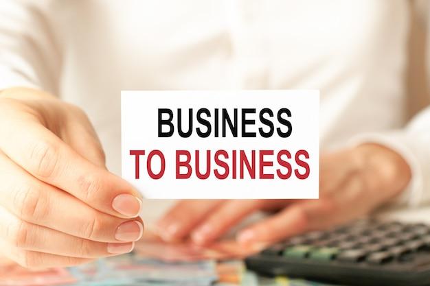 Business to business steht auf einer weißen visitenkarte. die hand einer frau hält eine weißbuchkarte vor dem weißen hintergrund. geschäfts- und werbekonzept. defokussieren.