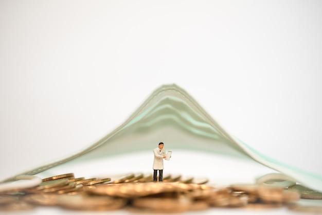 Business- und covid-19- und gesundheitskonzept. doktor miniaturfigur menschen mit patientenakte und stapel von goldmünzen unter chirurgischer gesichtsmaske mit kopienraum.