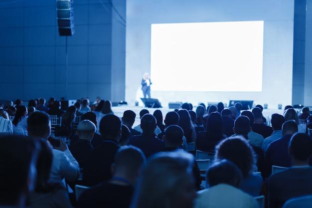 Business- und entrepreneurship-konzept. sprecher hält einen vortrag im konferenzsaal bei einer geschäftsveranstaltung. publikum im konferenzsaal. konzentrieren sie sich auf nicht wiedererkennbare personen