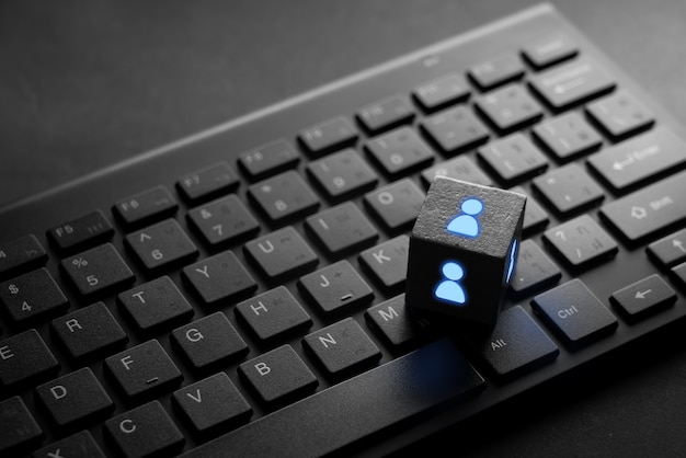 Business- und hr-symbol auf schwarzer computertastatur mit leuchten im dunkeln