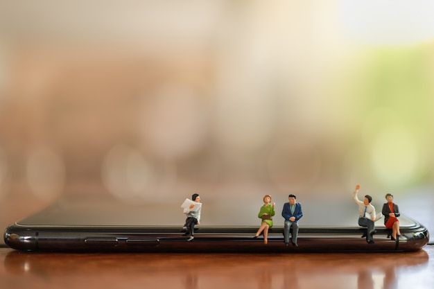 Business und kommunikation cencept. schließen sie oben von der gruppe von geschäftsmann- und frauenminiaturfigurenleuten, die auf dem intelligenten mobiltelefon sitzen, das mit zeitung mit kopienraum spricht.