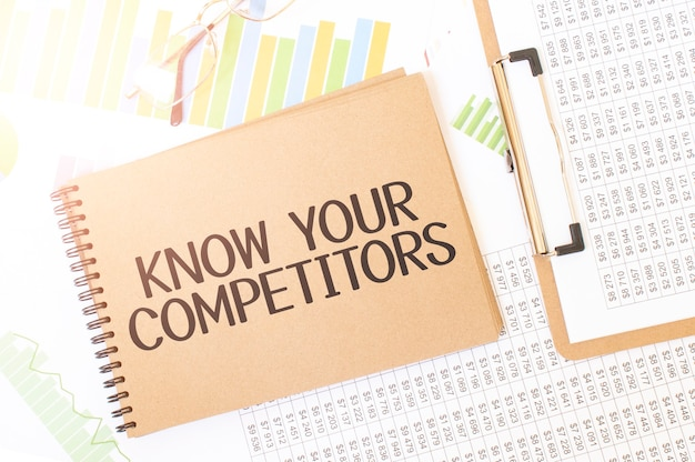 Business-up-grafik auf einem blatt craft color notepad mit know your competitors-zeichen. notizblock auf dem schreibtisch mit finanzdokumentation