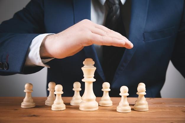 Businessbusinessma mit schachfiguren auf holzoberfläche