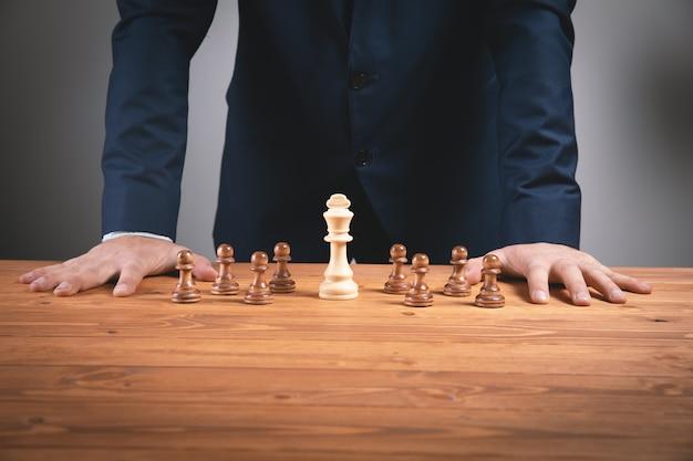 Businessma mit schachfiguren auf holzoberfläche