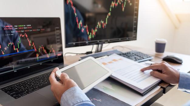 Businessman broker analysieren von grafiken und berichten zu finanzdaten auf dem bildschirm