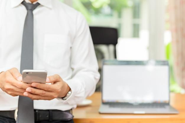 Businessmans-hand, die mobiltelefon mit laptop auf hölzernem schreibtisch hält