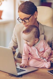 Businessplan mit mama machen. kleines mädchen mit laptop beim sitzen auf dem schreibtisch mit ihrer mutter im büro