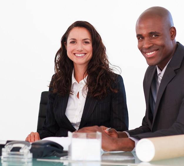 Businessteam in einer sitzung, welche die kamera betrachtet