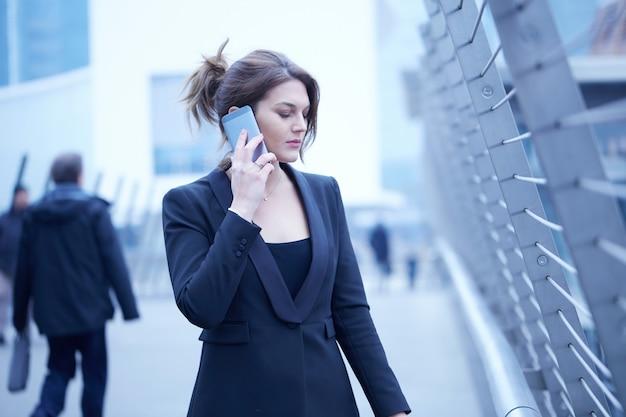 Businesswoma, das mit mobile in der städtischen umwelt spricht