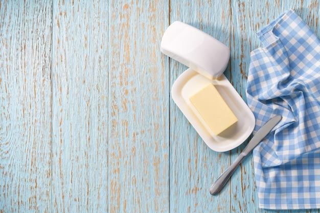 Butter auf butterdose auf blauem holztisch, draufsicht.