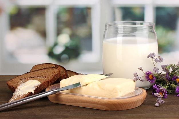 Butter auf holzhalter, umgeben von brot und milch auf holztisch