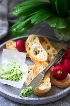 Butter mit bärlauch, brotscheiben und radieschen, zutaten für ein sandwich.