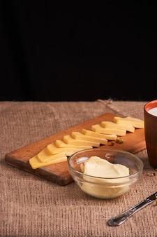 Butter und käse und milch zum frühstück über rustikalem holz