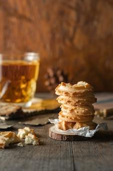 Butterkekse gestapelt und ein glas tee auf holztischhintergrund, vertikales foto.