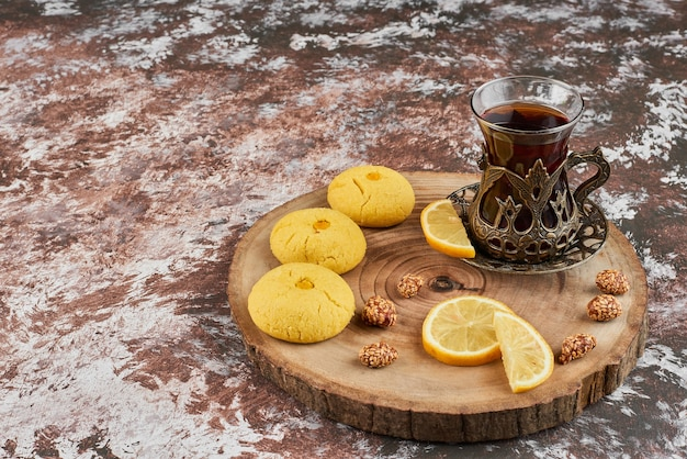 Butterkekse und ein glas tee auf einem holzbrett.