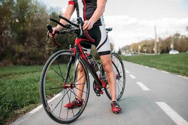 Bycyclist in helm und sportbekleidung beim fahrradtraining