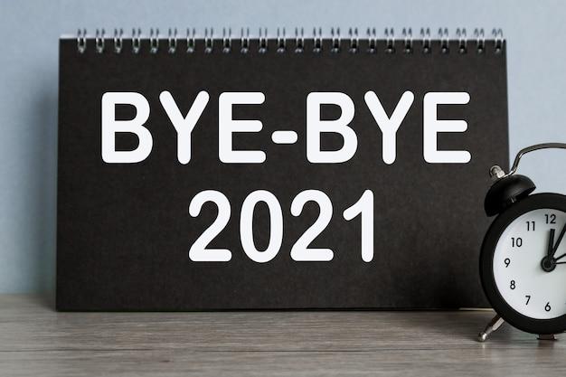 Bye-bye 2021 wecker, schwarzes notizbuch mit text, auf blauem hintergrund, zeit läuft weg.
