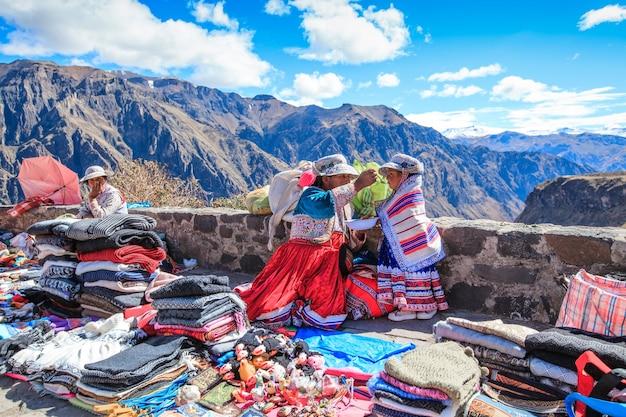 Cabanaconde, peru - 15. mai 2015: nicht identifizierte frauen verkaufen souvenirs am aussichtspunkt cruz del condor.