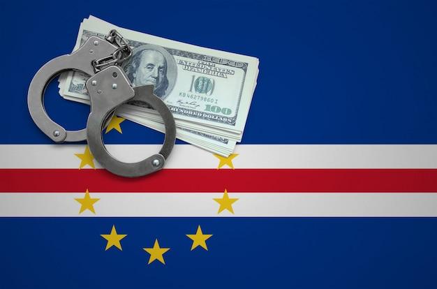 Cabo verde flagge mit handschellen und einem bündel dollar. das konzept, das gesetz zu brechen und verbrechen zu bestehlen