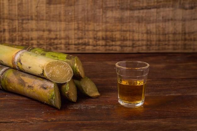 Cachaca ist der name eines typischen alkoholischen getränks, das in brasilien aus zuckerrohr hergestellt wird. traditionelles getränk aus brasilien auf holztisch