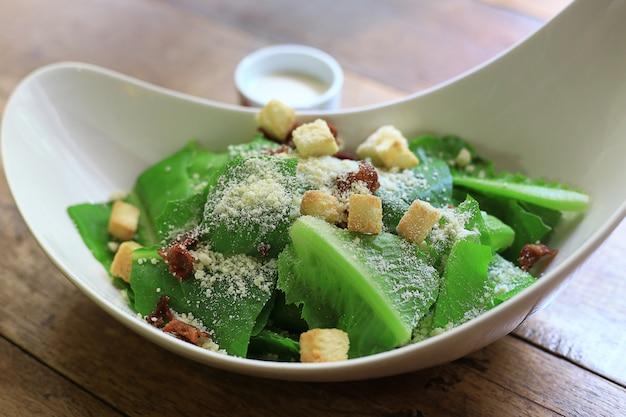 Caesar salad gesunde mittagsschüssel. mit soße in tassen auf holztisch hintergrund.