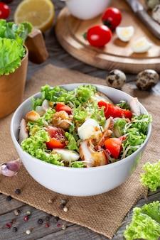 Caesar salad mit geräuchertem hühnchen und parmesan auf einem teller auf einem holztisch