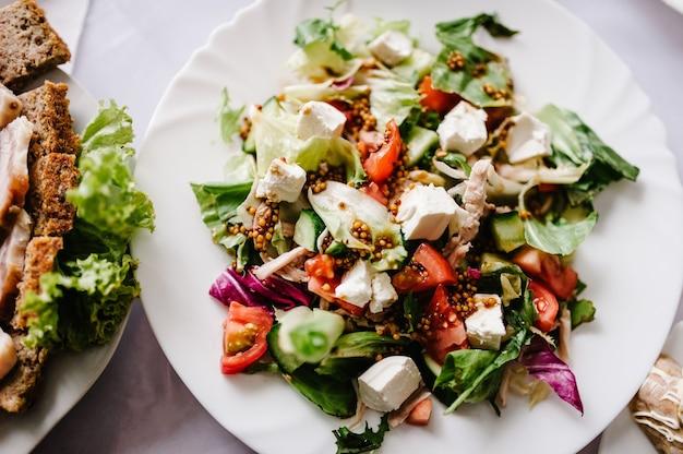 Caesar salat in einem weißen teller am hintergrund des tisches. nahansicht
