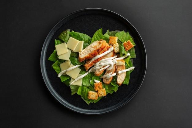 Caesar-salat in herzform, liebesessenkonzept, luxusplatte aus schwarzem stein, flaches design mit draufsicht, schwarzer hintergrund