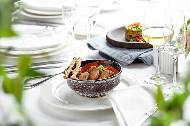 Caesar-salat mit brotstangen, wachteleiern, kirschtomaten und gegrilltem hühnchen in der platte auf weißem hintergrund.