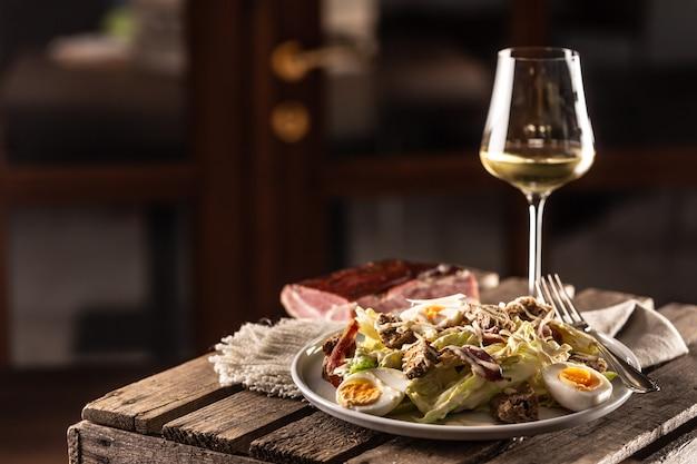 Caesar-salat mit croutons und ei serviert auf rustikalem holz mit einem glas weißwein.