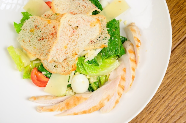 Caesar salat mit croutons, wachteleiern, kirschtomaten und gegrilltem hähnchen in holztisch. köstlicher salat mit hähnchen, nüssen, ei und gemüse.