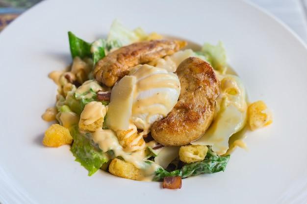 Caesar-salat mit frischem grünem gemüse wird mit gegrilltem hühnchen, gekochtem weißem ei und knusprigem brot gemischt. es ist ein gesundes ernährungskonzept.