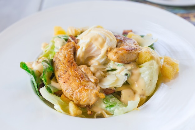 Caesar-salat mit frischem grünem gemüse wird mit gegrilltem hühnereiweiß und knusprigem brot gemischt