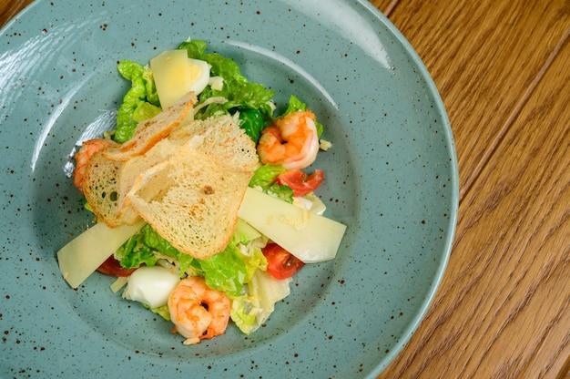 Caesar salat mit garnelen auf blauem teller auf hölzernem hintergrund. caesar salat mit garnelen, draufsicht