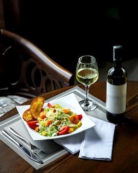 Caesar-salat mit garnelen und glas wein