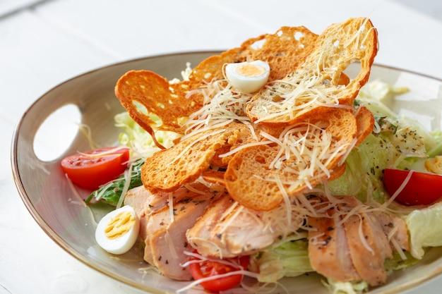 Caesar-salat mit gegrilltem hähnchen auf weißem holz
