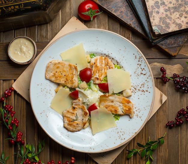 Caesar-salat mit gegrillten hähnchenbrust- und parmesanblättern