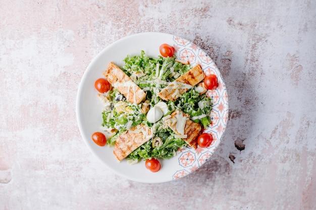Caesar salat mit gegrillter hähnchenbrust, parmesan und kirschtomaten.